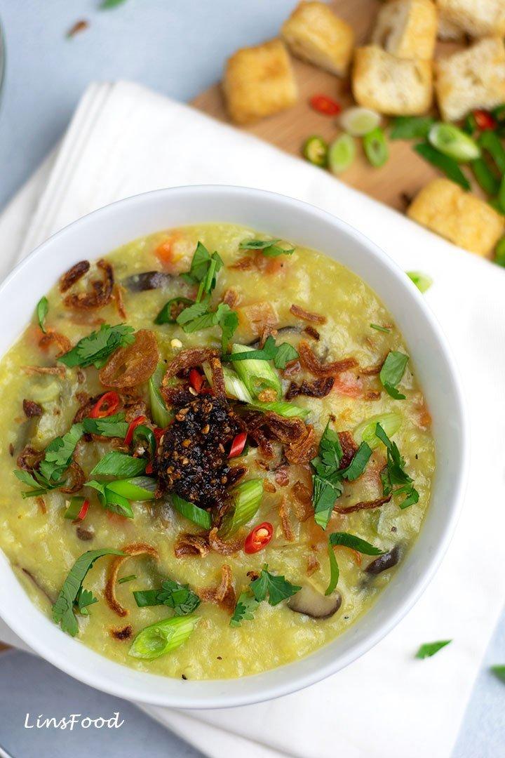 vegan bubur lambuk in white bowl with toppings